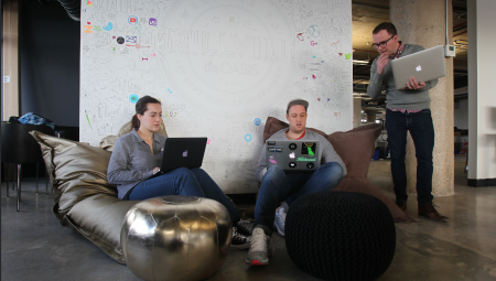 People sitting in formal bean bag chairs, discussing their laptops in front of a wall of logos.